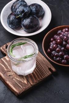 Vers ijskoud koolzuurhoudend water in glas op snijplank met rozemarijnblad in de buurt van houten kommen met druiven- en pruimvruchten, donkere stenen achtergrond, hoekmening