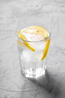 Vers ijskoud waterdrankje met citroen in glas op beton