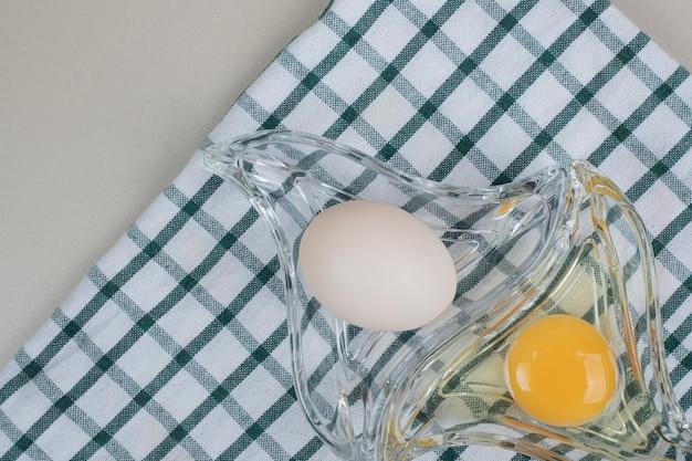 Vers kippen wit ei met dooier op glasplaat.