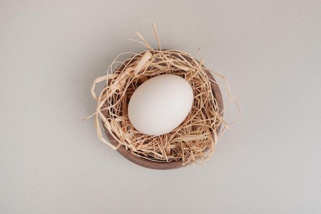 Vers kippen wit ei met hooi in houten kom.