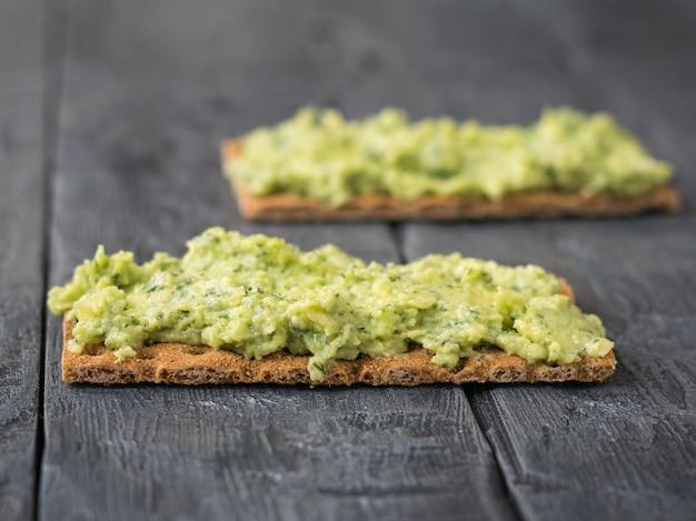 Vers knapperig brood met room en avocado op een rustieke houten zwarte lijst.