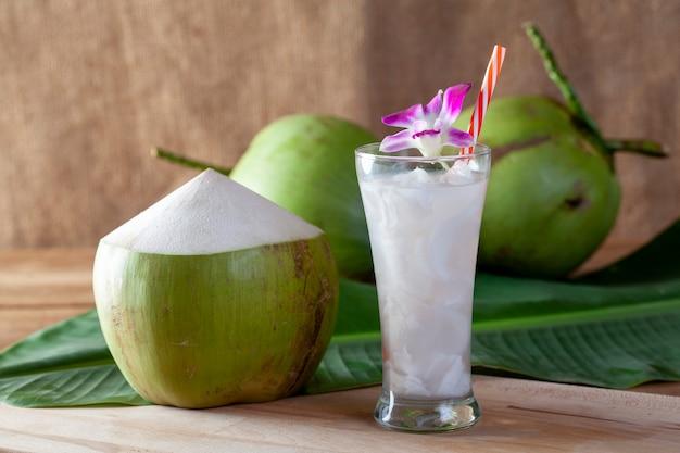 Vers kokosnotenwater in een glas op een houten raad voor het drinken