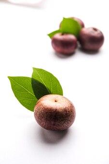 Vers kokum of garcinia indica fruit uit india geïsoleerd over wit of in rieten mand met bladeren. selectieve focus