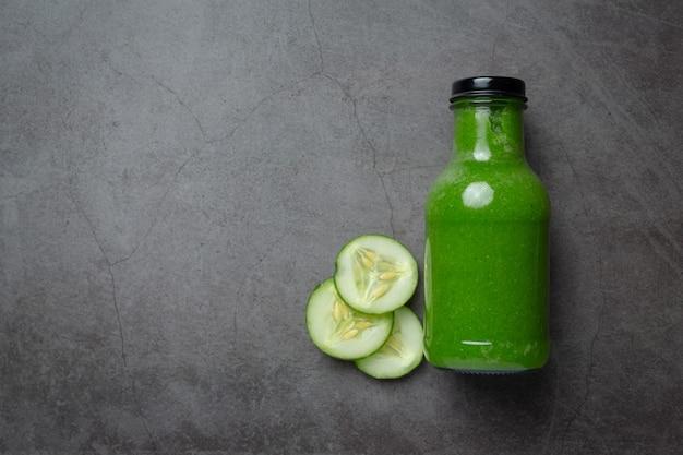 Vers komkommersap in een pot op donkere achtergrond