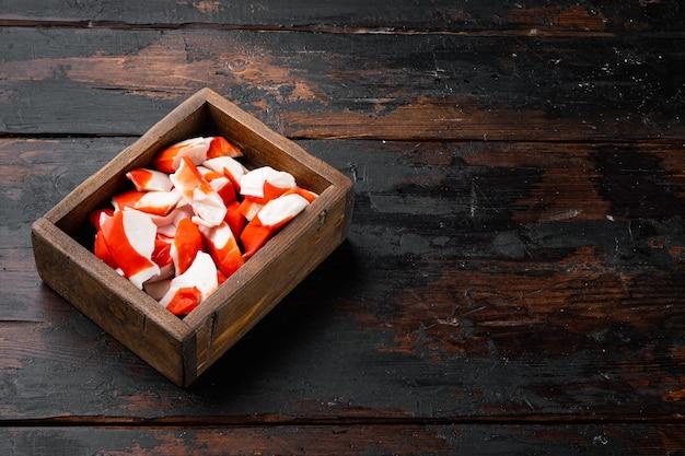 Vers krabvlees stick surimi met blauwe zwemmende krab set, in houten kist, op donkere houten achtergrond, met copyspace en ruimte voor tekst