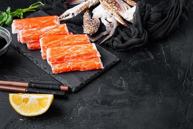 Vers krabvlees stick surimi met blauwe zwemmende krab set, op stenen bord, op zwarte achtergrond, met copyspace en ruimte voor tekst