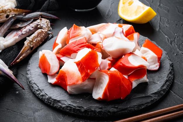 Vers krabvlees stick surimi set, op stenen bord, op zwarte tafel