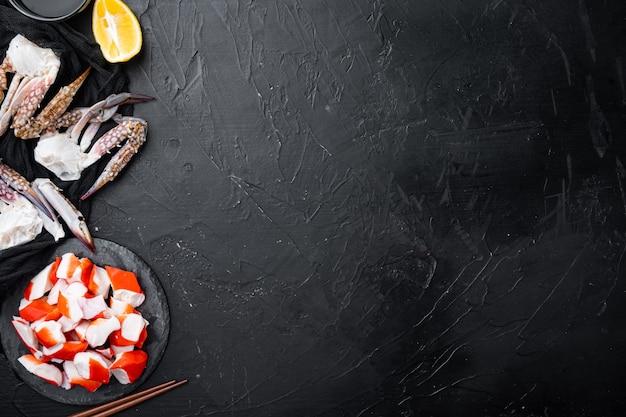 Vers krabvlees surimi met blauwe zwemmende krab set, op stenen bord, op zwarte achtergrond, bovenaanzicht plat lag, met copyspace en ruimte voor tekst