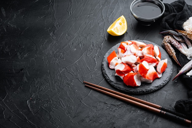 Vers krabvlees surimi met blauwe zwemmende krab set, op stenen bord, op zwarte achtergrond, met copyspace en ruimte voor tekst