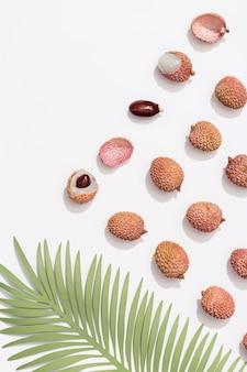 Vers litchifruit en palmblad op witte achtergrond minimaal fruit en de zomerconcept