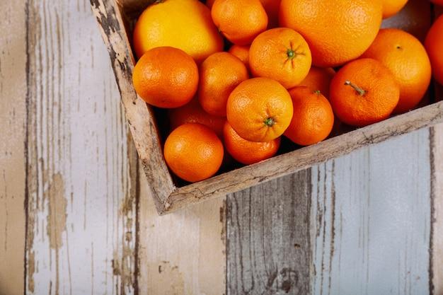 Vers mandarijnen in oude doos met op houten achtergrond.