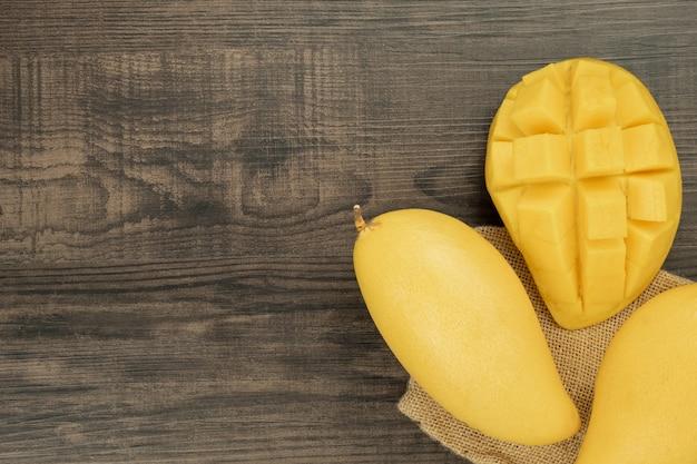 Vers mango bovenaanzicht. houten achtergrond en kopie ruimte voor tekst toevoegen.