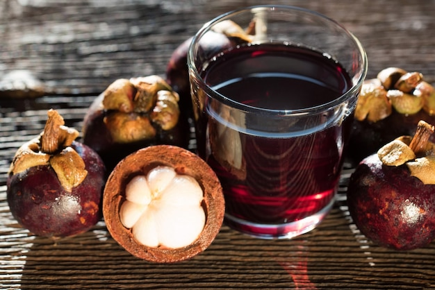Vers mangosteenvrucht en drank in kruik op houten achtergrond