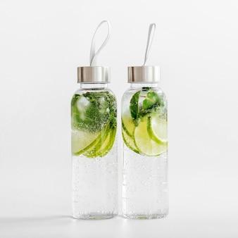 Vers met limoen en munt doordrenkt water, cocktail, detoxdrank, limonade in herbruikbare flessen. zomerse drankjes. gezondheidszorgconcept.