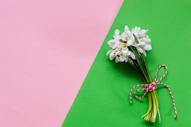 Vers mooi boeket van de eerste lente bos sneeuwklokjes bloemen met rode en witte koord martisor