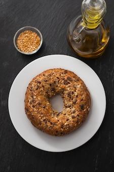 Vers ongezuurd broodje met zaden op witte plaat op keramiek