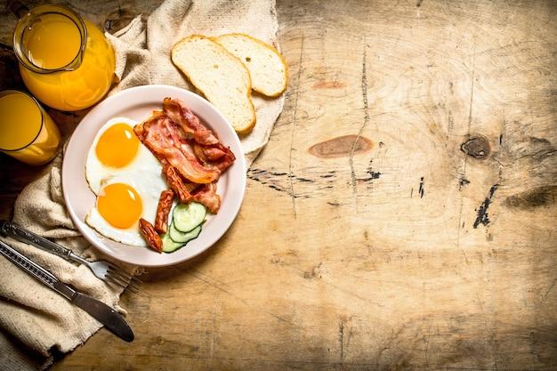 Vers ontbijt. jus d'orange met gebakken eieren, spek en sneetjes brood. op een houten tafel.