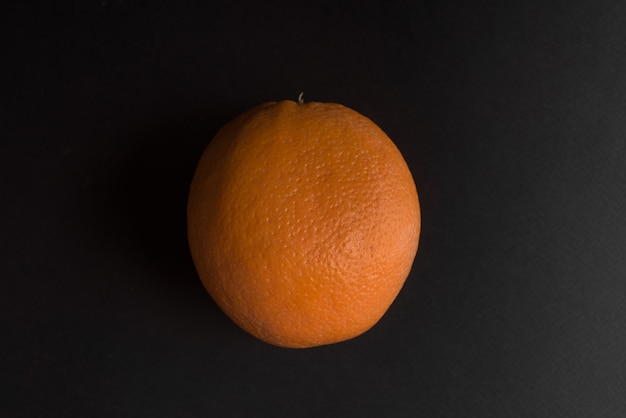 Vers oranje fruit dat over zwarte wordt geïsoleerd
