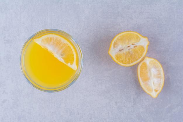 Vers oranje fruit en sap op marmeren tafel.