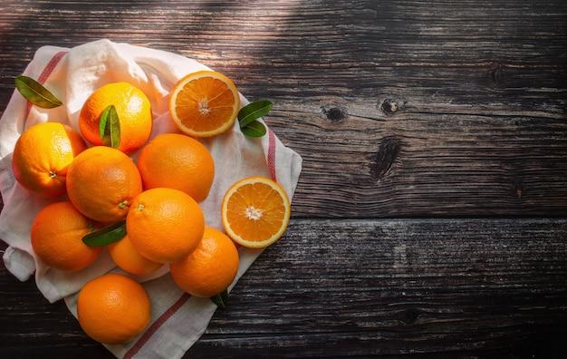 Vers oranje fruit met bladeren op houten tafel en zonlicht ochtend.