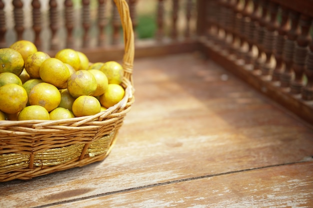 Vers oranje mandarijnfruit in rotan rieten mand op houten stoel