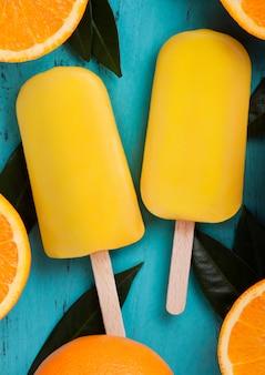 Vers organisch fruit oranje roomijs met bladeren met verse sinaasappelen op blauwe houten achtergrond.
