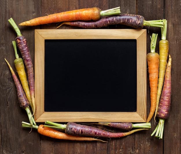 Vers organisch regenboogwortelen en bord op een houten mening van de lijstbovenkant