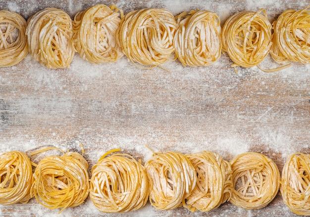 Vers pastavoedsel. zelfgemaakte italiaanse pasta gekookt op een houten tafel in een rustieke stijl versierd met ei en meel.