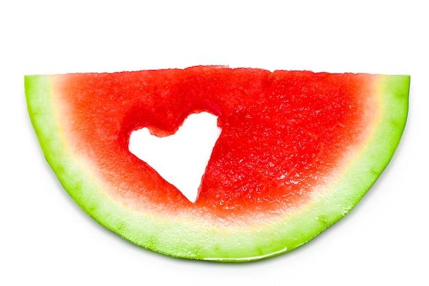 Vers plakje watermeloen met hart geïsoleerd op een witte achtergrond.
