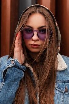 Vers portret cool hipster jonge vrouw in glamoureuze paarse bril in mode jeugd oversized denim jasje in de buurt van moderne metalen rode muur. europees meisje rechtzetten trendy camouflage kap in de stad.