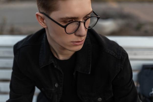 Vers portret europese jongeman met schone, gezonde huid in stijlvolle bril in zwarte modieuze spijkerjas op straat. vrij moderne stedelijke man mannequin buitenshuis. jeugd stijl.