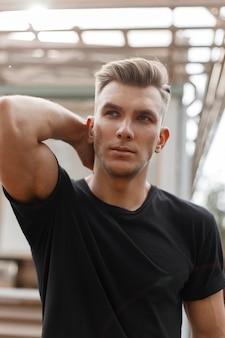 Vers portret van modieuze knappe jonge stijlvolle model man met kapsel in zwart t-shirt op straat