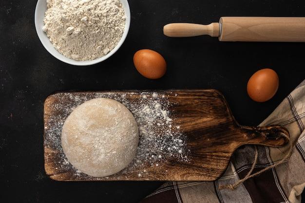 Vers rauw deeg voor brood of pizza met eieren op een donkere achtergrond met bloem bestuiven.