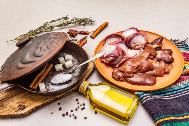 Vers rauw eendenafval: hart, lever, maag. droge kruiden, zout, suiker, olie. frituurpan,