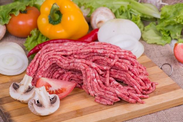 Vers rauw gehakt vlees op een snijplank met groenten en groenen