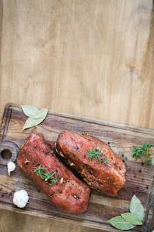 Vers rauw gemarineerd vlees op een houten tafel.