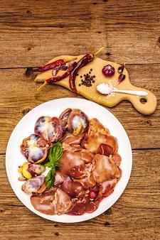 Vers rauw kippenafval: hart, lever, maag met droge kruiden, zeezout, spaanse peper op houten tafel