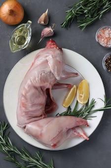 Vers rauw konijn met olijfolie, rozemarijn, paprika, knoflook, zeezout en citroen op witte plaat op grijze ondergrond. bovenaanzicht. verticaal formaat.