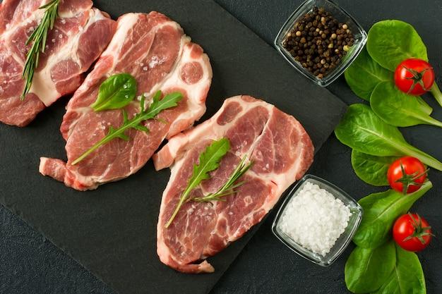 Vers rauw pork chop vlees op een plack leisteen met rozemarijn en peterselie en zwarte peper.