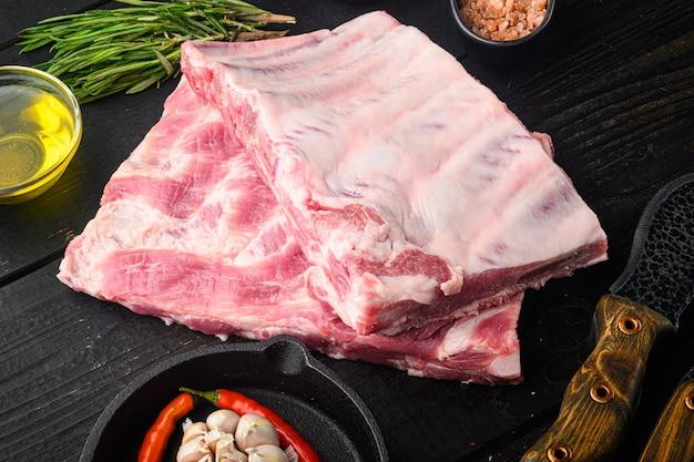 Vers rauw varkensvlees van biologische boerderij met kruidenset, met honing, met barbecuemes en vleesvork, op zwarte houten tafel, met kopieerruimte voor tekst