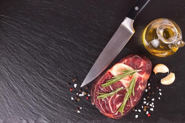 Vers rauw vlees biefstuk met bot met kruiden, rozemarijn, mes en olijfolie