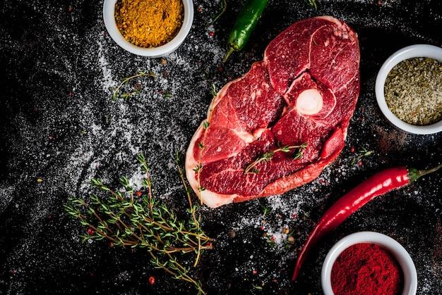 Vers rauw vlees. een stuk ossenhaas, met een bot, met een snijbijl, met kruiden om op een oude roestige zwarte metalen tafel te koken bovenaanzicht