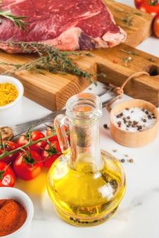 Vers rauw vlees, lamsbiefstuk marmeren steak op een snijplank, met ingrediënten voor het koken. op witte marmeren tafel, copyspace