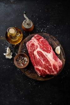 Vers rauw vlees met kruiden en zout op donkere rustieke achtergrond.