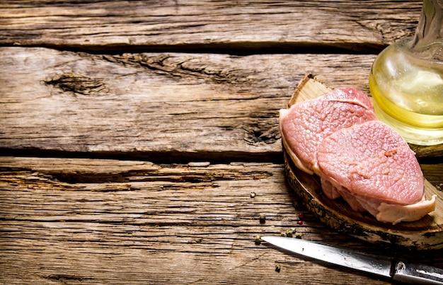 Vers rauw vlees met mes en olie op een houten standaard op een houten tafel