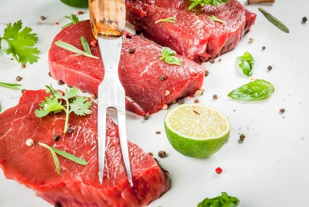 Vers rauw vlees. ossenhaas, steaks, op een witte marmeren tafel. met olijfolie, kruiden om te koken - basilicum, rozemarijn, koriander, peterselie, knoflook, citroen, zout, peper. kopieer ruimte