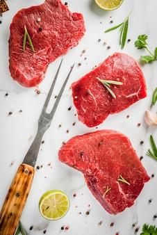 Vers rauw vlees. ossenhaas, steaks, op een witte marmeren tafel. met olijfolie, kruiden voor het koken van basilicum, rozemarijn, koriander, peterselie, knoflook, citroen, zout, peper. bovenaanzicht copyspace