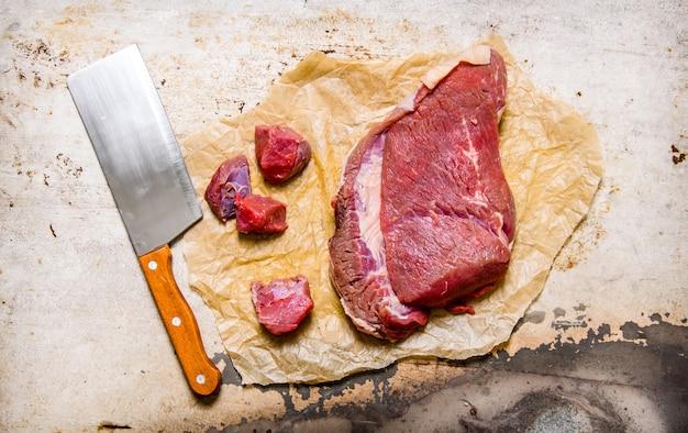 Vers rauw vlees snijden op papier. op de rustieke achtergrond. bovenaanzicht