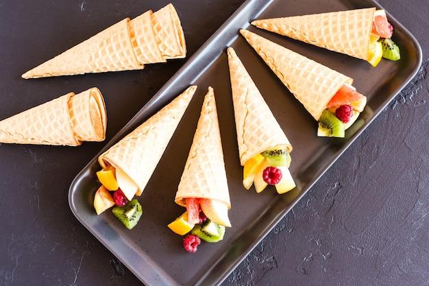 Vers rijp fruit in wafelkegels. feestelijk dessert. zoete traktatie.
