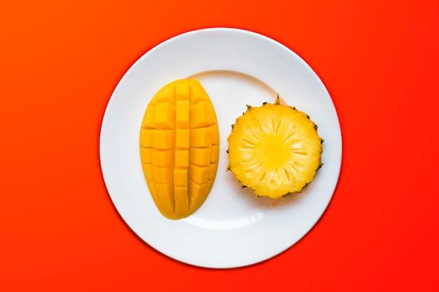 Vers rijp tropisch exotisch fruit: geel zoete smakelijke mango geschild, in vierkanten gesneden en ananas segment op een witte plaat. bovenaanzicht, gezond veganistisch eten